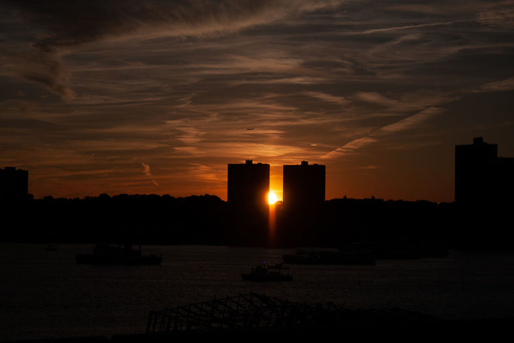 Silhouette buildings by sea against sky during sunset
