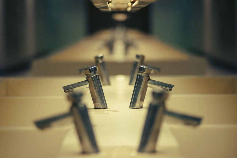 Row Of Faucets With Reflection In Restroom