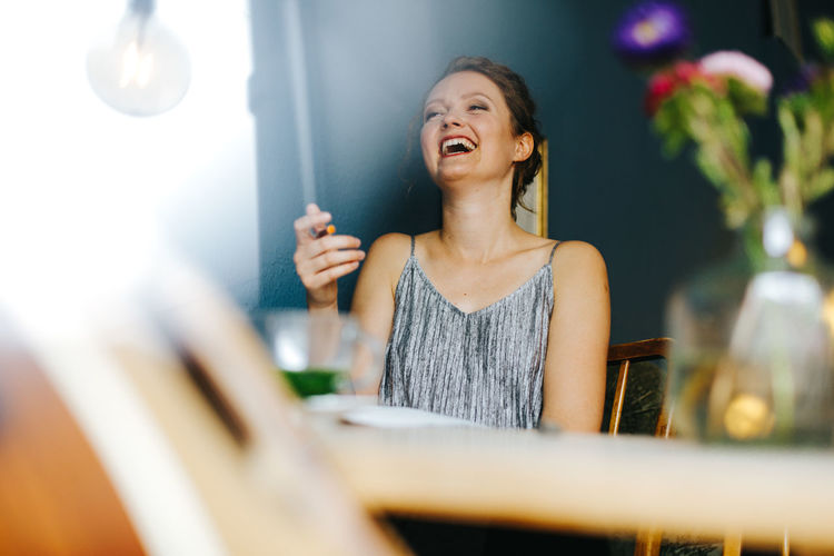 young blonde woman laughing Woman Cheerful Day Drink Enjoyment Food And Drink Front View Fun Happiness Holding Indoors  Leisure Activity Lifestyles One Person People Real People Refreshment Selective Focus Smiling Table Woman Portrait Young Adult Young Women