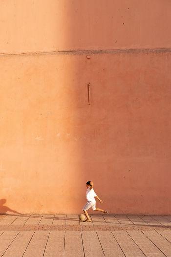 Woman sitting on footpath against wall