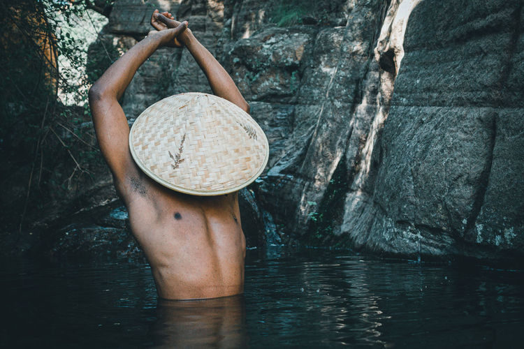 Midsection of man with straw hat in water