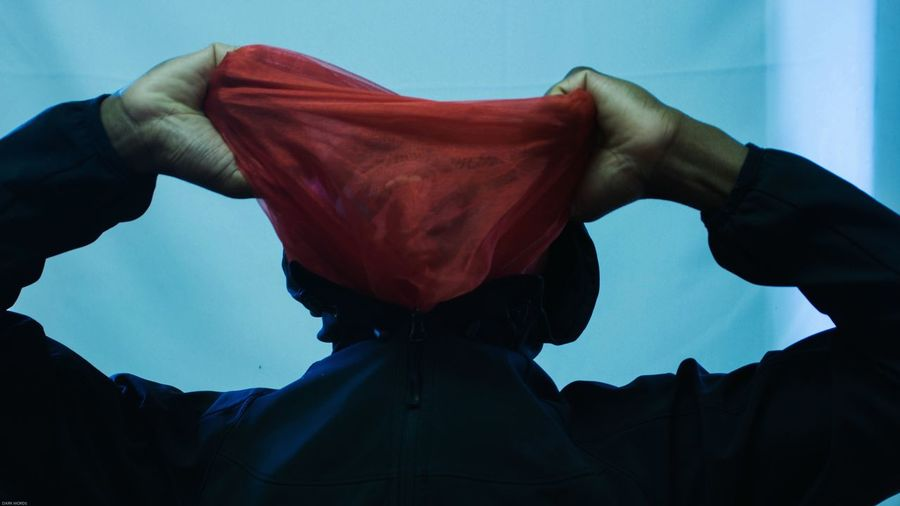 Low angle view of man holding red textile in front of face while standing