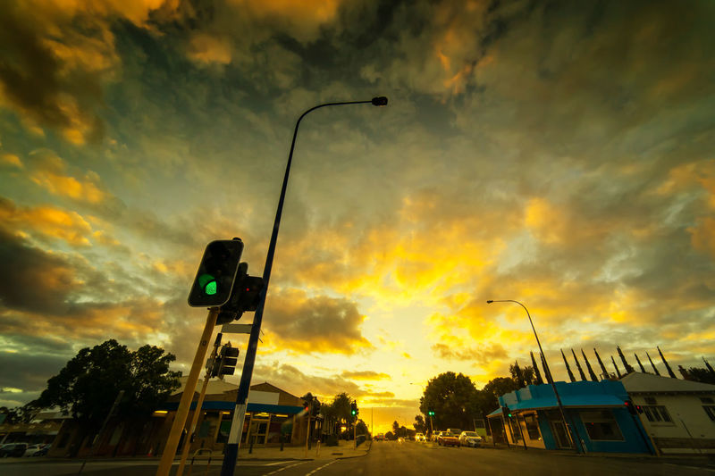Architecture Building Exterior Built Structure Car City Cloud - Sky Guidance Illuminated Light Low Angle View Mode Of Transportation Motor Vehicle No People Outdoors Road Road Signal Sign Sky Stoplight Street Street Light Sunset Transportation