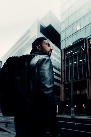 Low angle view of man looking at modern building in city