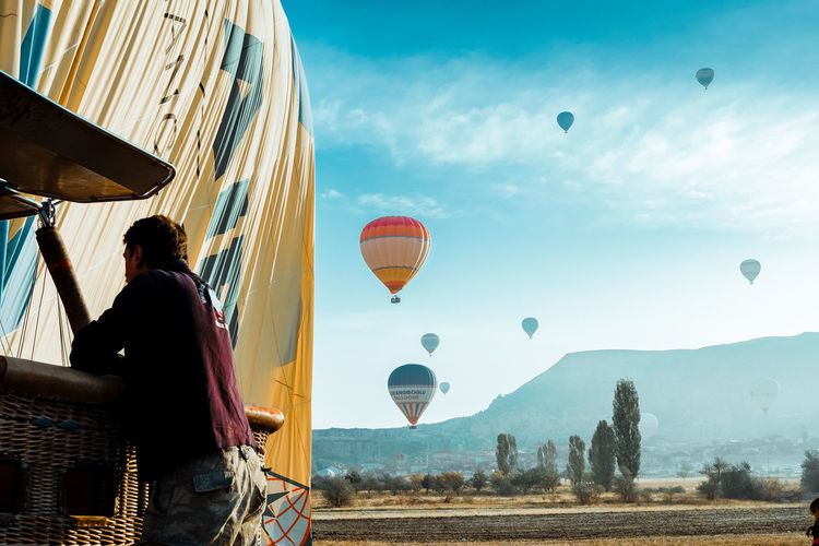 Rear view of man with hot air balloons flying in sky