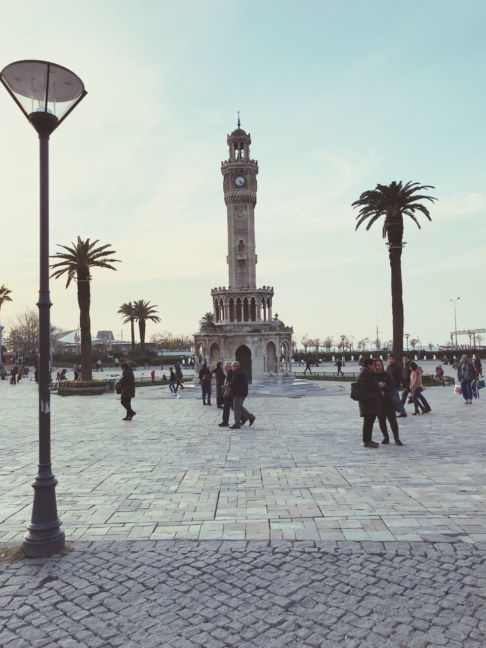 architecture, building exterior, sky, group of people, city, built structure, street, tourism, real people, travel destinations, crowd, travel, large group of people, history, cobblestone, the past, nature, lifestyles, city life, palm tree, outdoors, paving stone