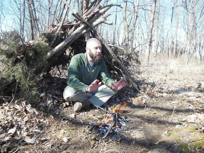 Bearded man sitting by campfire in forest