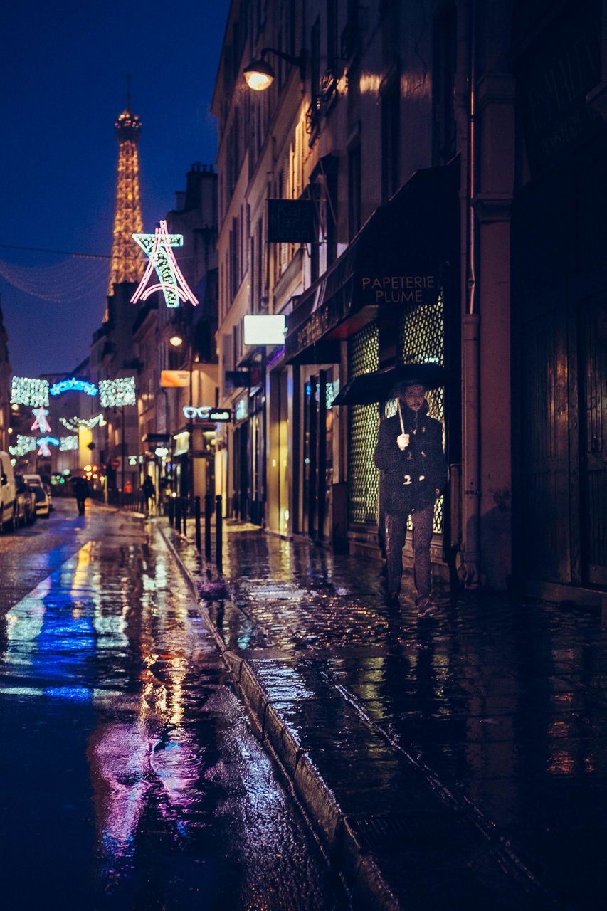 rain, wet, night, rainy season, built structure, illuminated, weather, architecture, building exterior, water, outdoors, street, protection, real people, under, city, sky