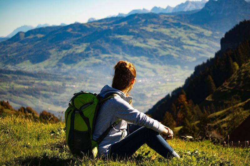 Side view of young woman with backpack sitting on mountain
