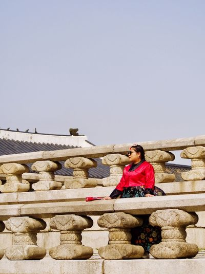 Woman sitting against built structure against clear sky