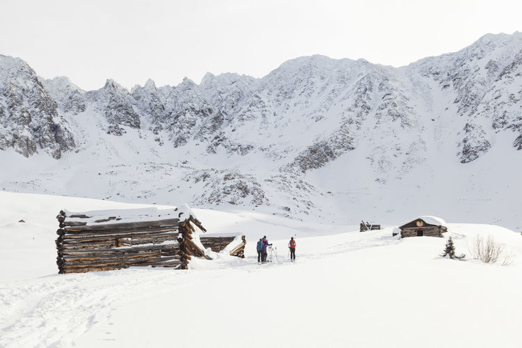 Rear view of people on snowcapped mountains against sky
