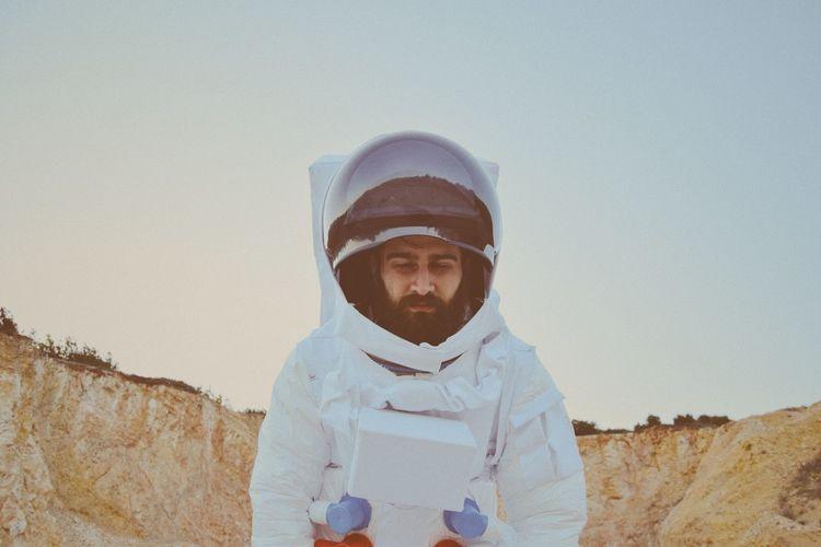 Astronaut on land against sky