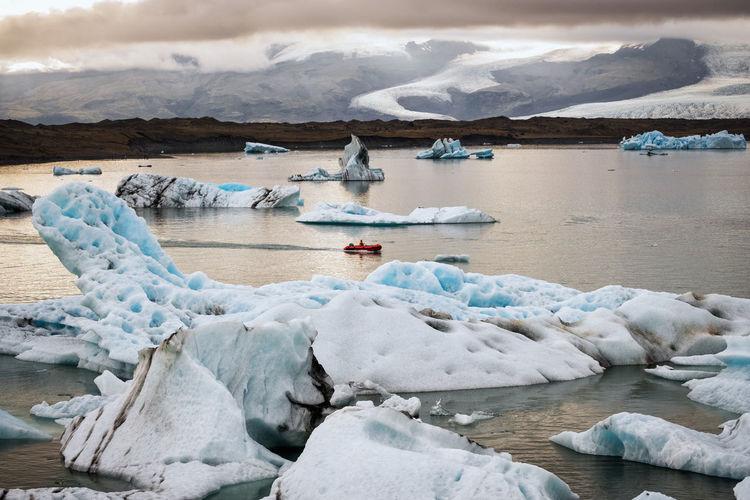 Icebergs in sea against sky