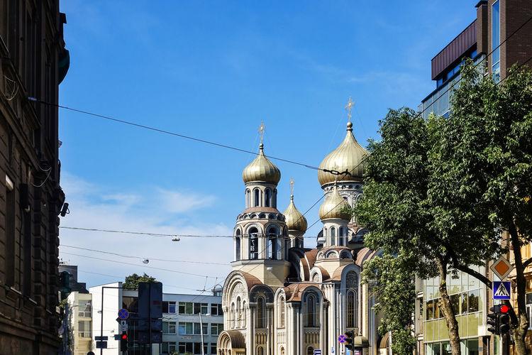 Buildings and church against blue sky