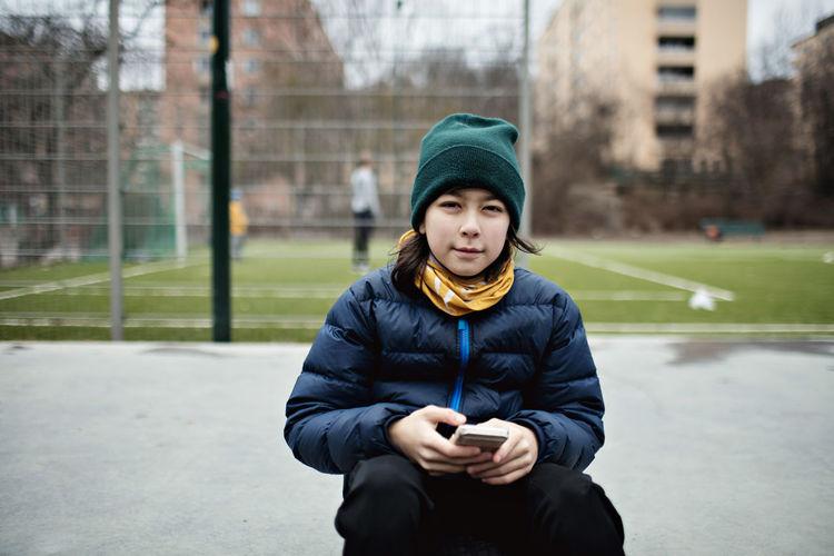 Portrait of teenage girl standing in city during winter
