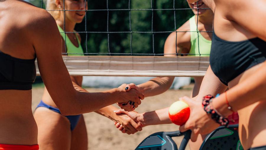 Beach tennis players congratulating each other after match