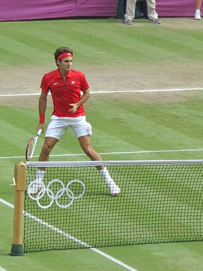WIMBLEDON, ENGLAND - August 2nd, 2012 - Roger Federer during one of his singles matches at the summer Olympics in London in 2012. He came 2nd and won the silver medal in the tournament. Federer Tennis Athlete Ball Clothing Competition Court Day Grass Leisure Activity Men Net - Sports Equipment One Person Playing Playing Field Red Roger Federer Sport Sports Uniform Standing Tennis Net Young Adult Young Men
