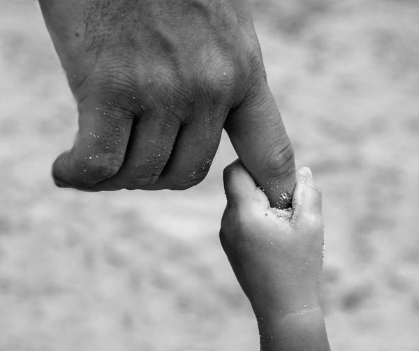 Close-Up Of Father And Son Holding Hands