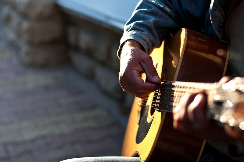 Midsection of street musician playing guitar