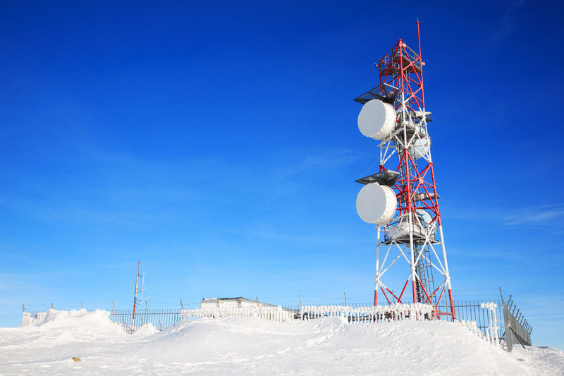 Low Angle View Of Communication Tower On Snow Field Against Blue Sky