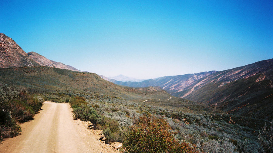 35mm 35mm Film Blue Clear Sky Country Road Countryside Day Diminishing Perspective Dirt Road Empty Road Landscape Mountain Mountain Range Nature No People Offroad Outdoors Road Sky The Way Forward Travel