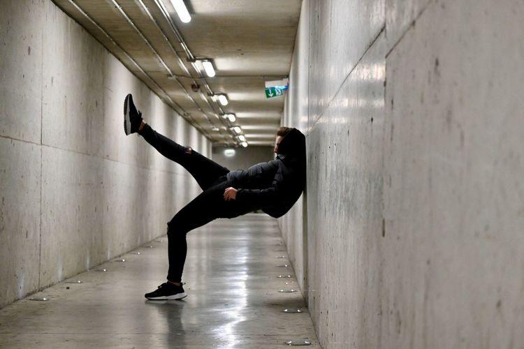 Side view of boy raising leg in a corridor