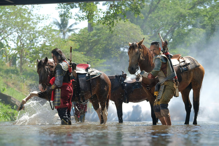 People riding horses in water