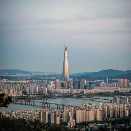 Modern Skyscraper Amidst Cityscape Against Sky