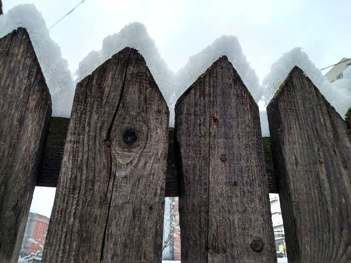 Wooden fence in winter against sky