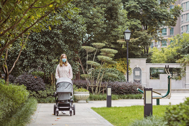 Woman standing on footpath in park