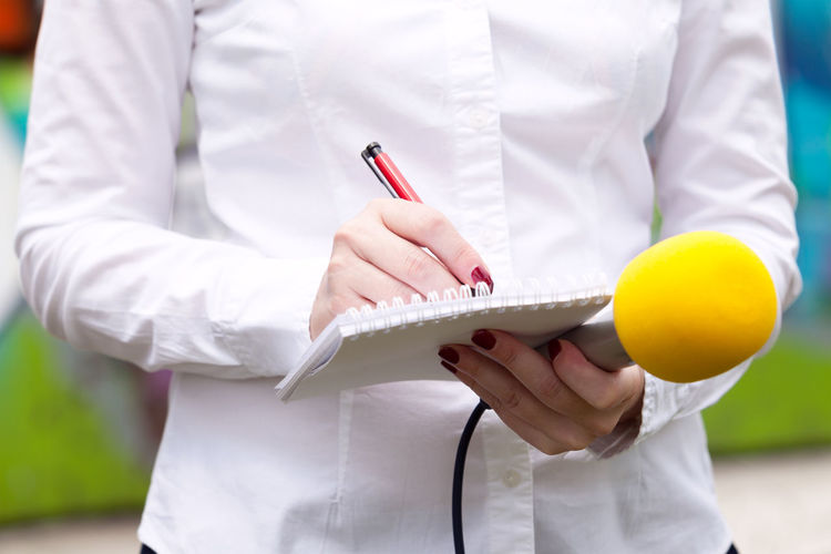 Female reporter at press conference, writing notes, holding microphone Tv Event Interview Journalist Press Woman Writing Audio; Broadcast Broadcasting Conference Correspondent Female Information Journalism Media Microphone News Newspaper Notebook Notes Pen Report Reporter