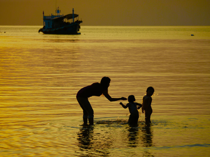 Mother playing with kids in sea during sunset