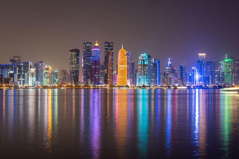 Illuminated buildings of doha city against sky at night