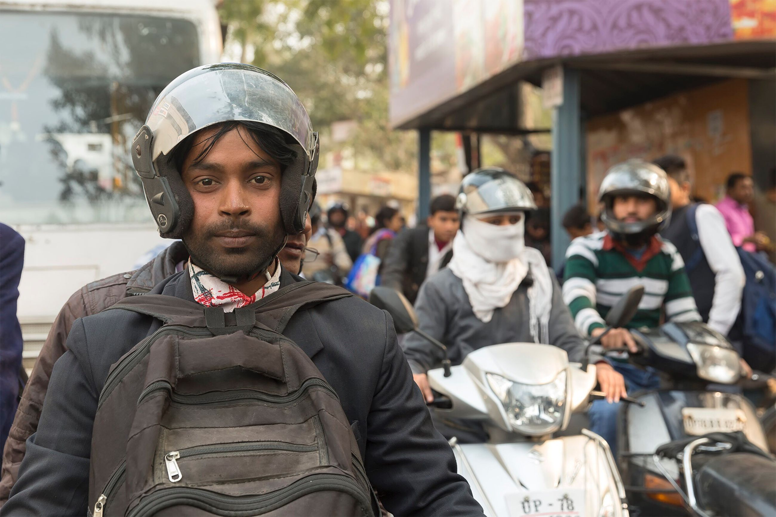 real people, front view, looking at camera, portrait, focus on foreground, day, standing, lifestyles, men, helmet, outdoors, headwear, one person, young adult, people