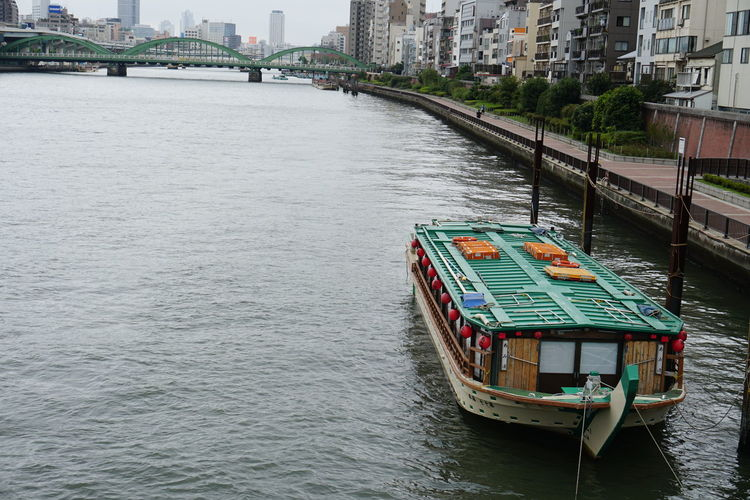 Boat sailing on river in city