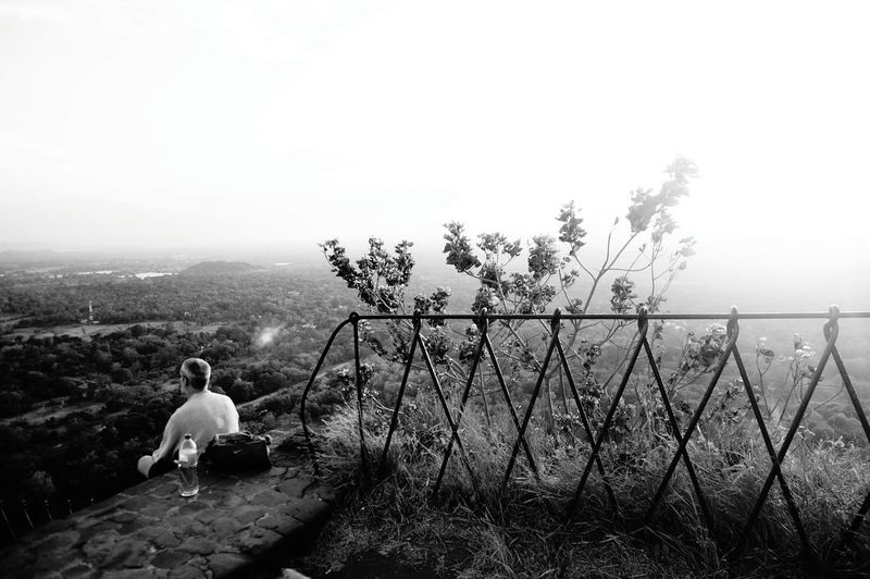 High angle view of man sitting on rock against sky