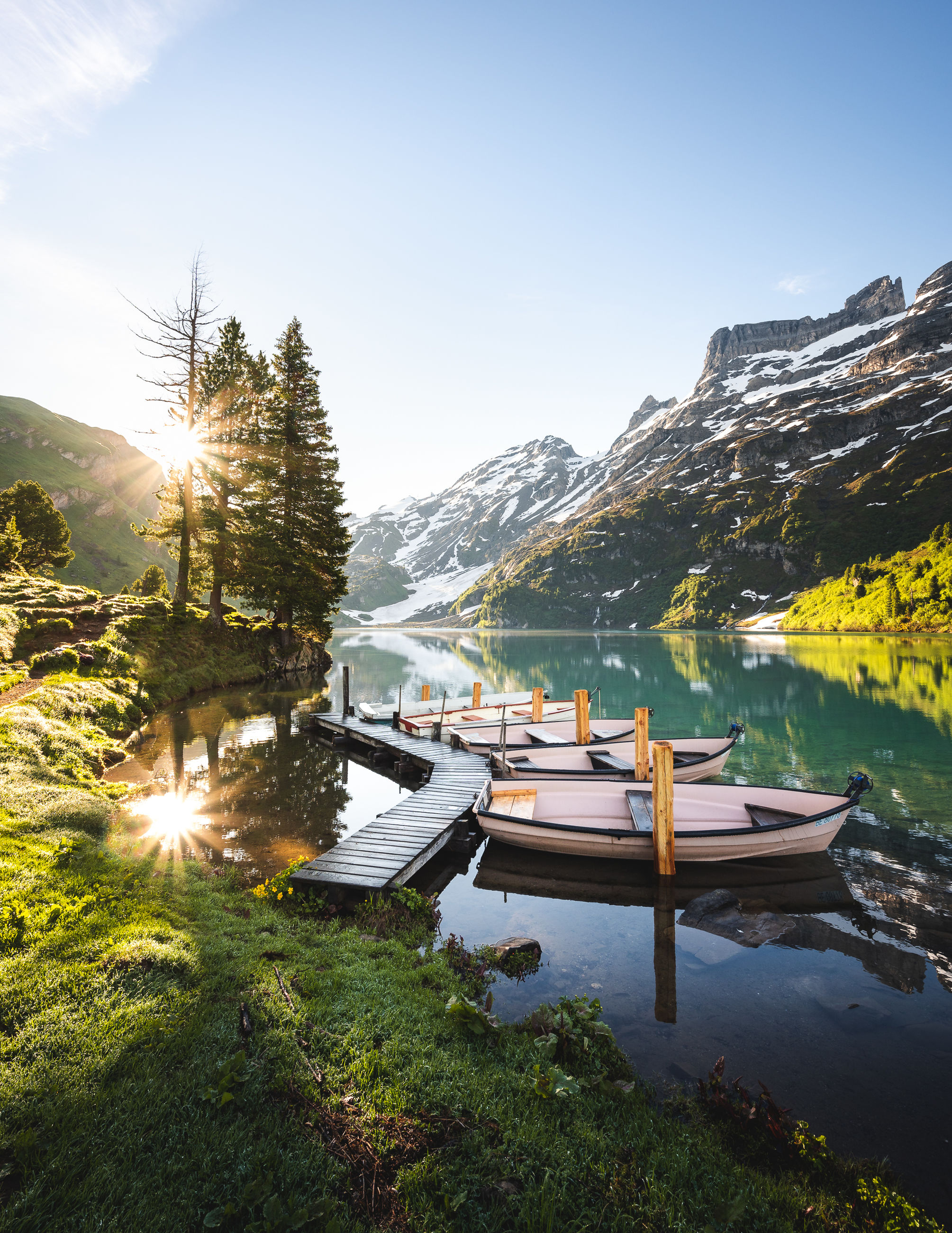 water, mountain, scenics - nature, sky, nature, beauty in nature, reflection, lake, landscape, environment, tranquility, sunlight, mountain range, plant, nautical vessel, travel, land, tranquil scene, travel destinations, transportation, tree, sun, no people, snow, wilderness, forest, lens flare, outdoors, cold temperature, day, pinaceae, winter, vacation, sunbeam, idyllic, non-urban scene, clear sky, sunny, coniferous tree, summer, trip, adventure, activity, holiday, tourism, blue, pine tree, mountain peak, sunset, mode of transportation, grass, twilight, leisure activity