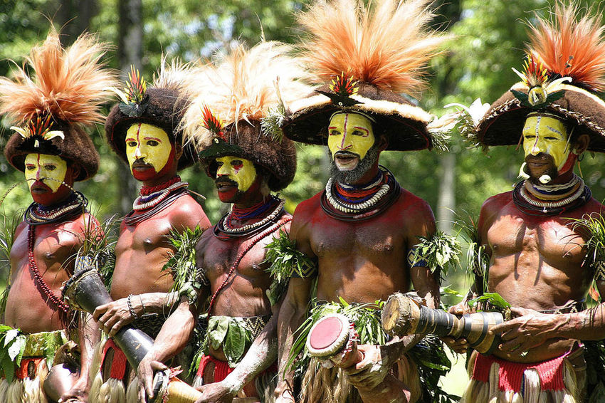 A troupe of Papau New Guinea drummers from one of the highland tribes - Papua New Guinea, Australasia Papua New Guinea Tribesmen Bare Chests Canibalism Day Feathers In Hair Human Representation No People Outdoors Painted Faces Sculpture Statue Tribal Drums Yellow Faced