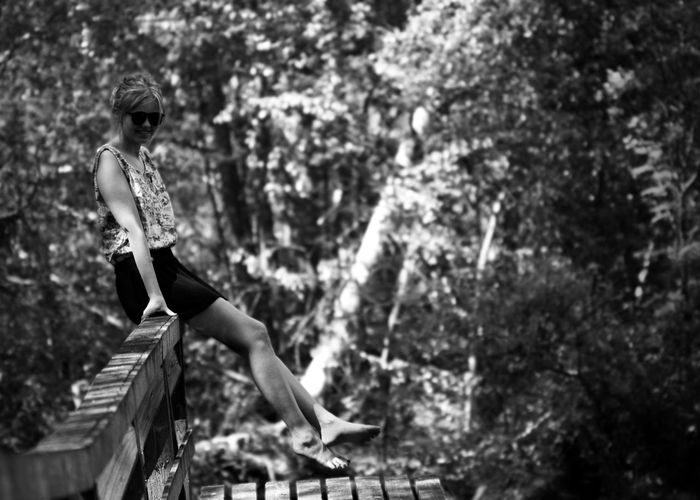 Portrait of woman sitting on railing against trees