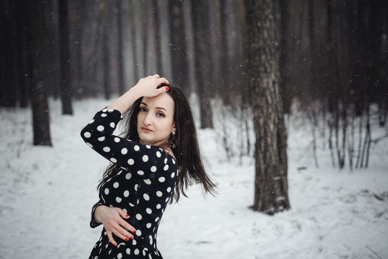 Portrait Of Beautiful Woman Standing In Forest During Winter