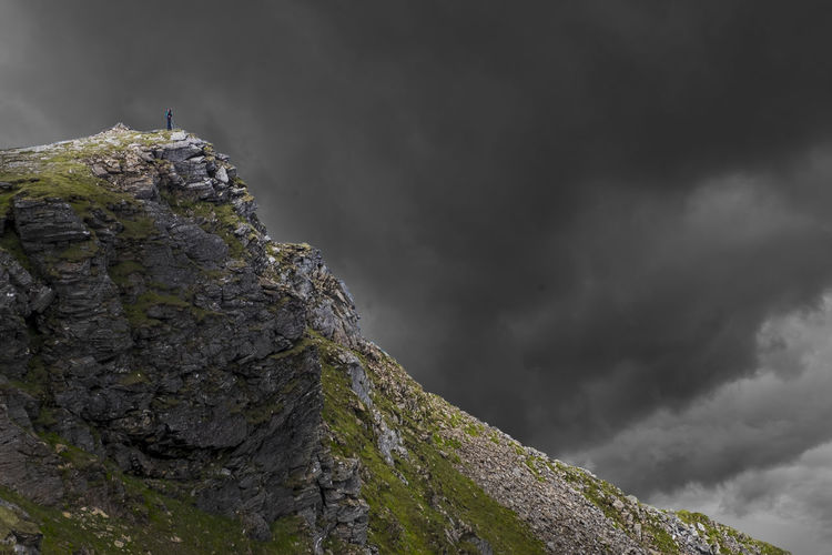 Distant view of woman standing on mountain against cloudy sky