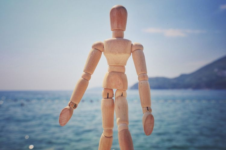 Close-up Of Wooden Figurine Against Sea