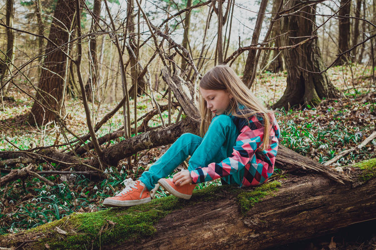 Side View Of Little Girl Tying Shoelace While Sitting On Log In Forest