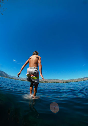 Rear View Of Boy Diving Into Lake Chelan Against Blue Sky