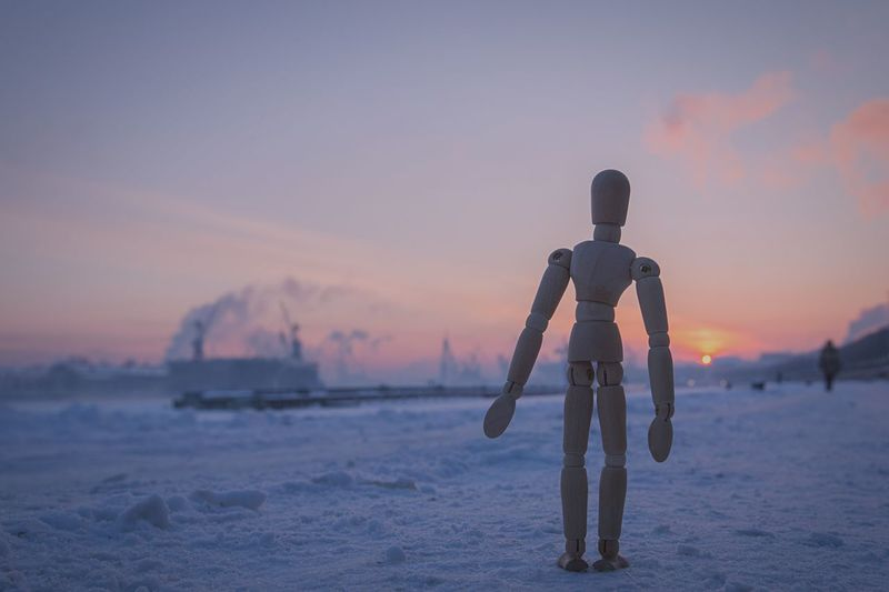 Close-Up Of Wooden Figurine On Snow Covered Field Against Sky At Sunset