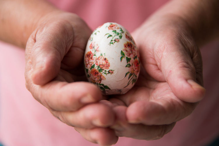 Midsection of woman holding ester egg in hand