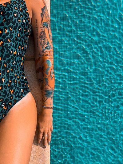 Midsection of woman relaxing at edge of swimming pool