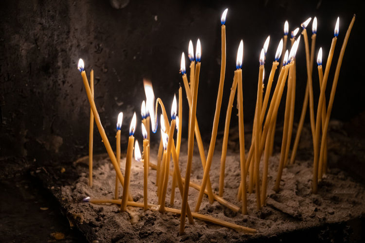 Close-up of burning candles in temple against building