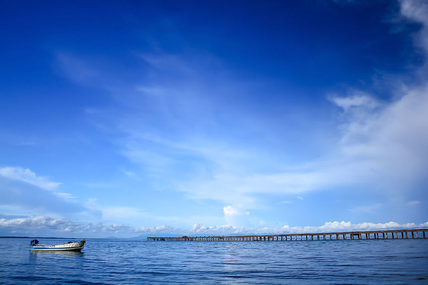 Small white boat in the sea. Bridge Over Water Bridges Architecture Beauty In Nature Blue Bridge View Built Structure Cloud - Sky Day Landscape Sea Landscape Sea Nature Outdoors Landscape Seascape Nature No People Non-urban Scene Outdoors Pier Scenics - Nature Sea Sky Tranquil Scene Tranquility Transportation Water Waterfront