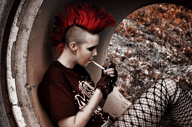Side view of punk woman smoking cigarette while sitting in pipe